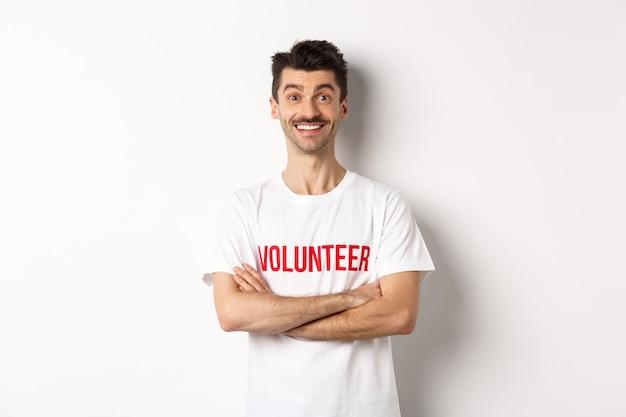 Gelukkig jonge man in vrijwilligers t-shirt klaar om te helpen, glimlachend in de camera, kruis armen op borst zelfverzekerde, witte achtergrond