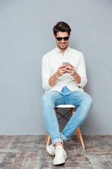 Gelukkig jonge man in zonnebril zitten en luisteren naar muziek van smartphone
