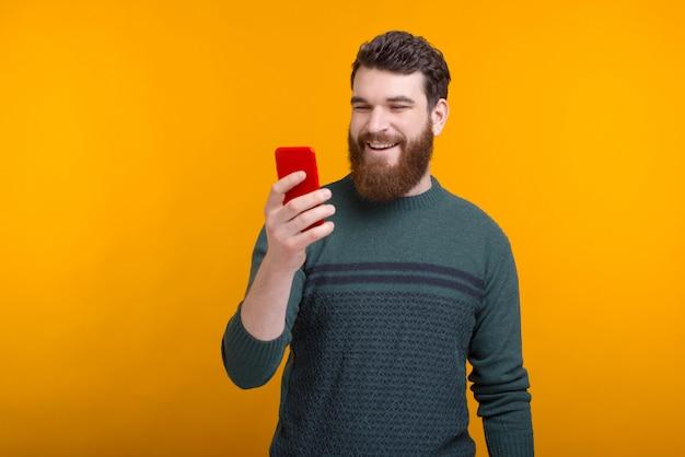 Gelukkig jonge man kijkt naar de telefoon, video praten over gele ruimte.