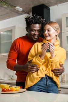 Gelukkig jonge man lachen en knuffelen zijn geliefde vriendin terwijl ze met haar in de keuken staat
