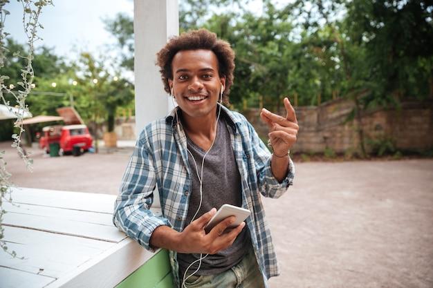Gelukkig jonge man, luisteren naar muziek van mobiele telefoon en plezier