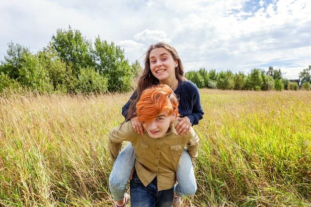 Gelukkig jonge man meeliften zijn vriendin buiten in de zomer.