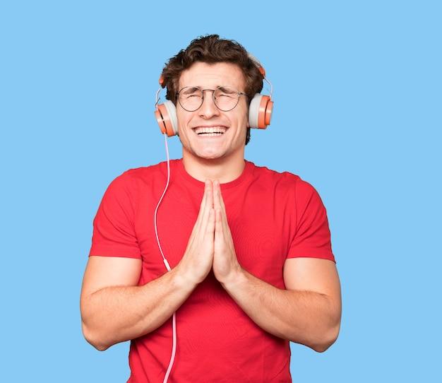 Gelukkig jonge man met behulp van koptelefoon en een smartphone en een gebed gebaar maken