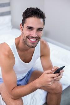 Gelukkig jonge man met behulp van mobiele telefoon op bed