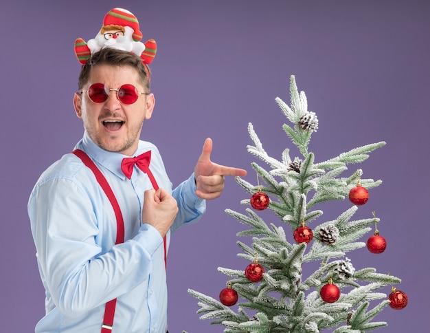 Gelukkig jonge man met bretels strikje in rand met kerstman en rode bril permanent naast kerstboom wijzend met wijsvinger naar kijken camera glimlachen op paarse achtergrond