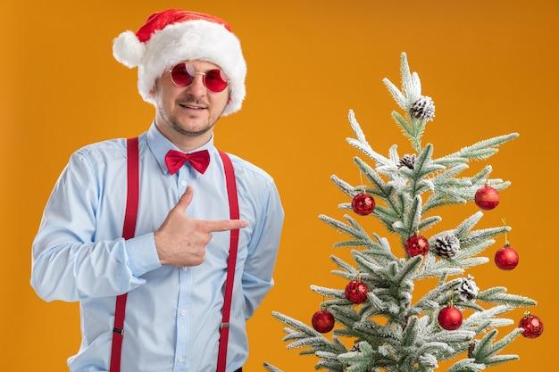 Gelukkig jonge man met bretels vlinderdas in kerstmuts en rode bril staande in de buurt van de kerstboom wijzend met wijsvinger naar het glimlachend over oranje muur