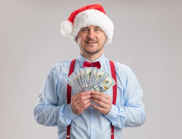 Gelukkig jonge man met bretels vlinderdas in kerstmuts met contant geld kijken naar de camera met een glimlach op het gezicht staande op een witte achtergrond
