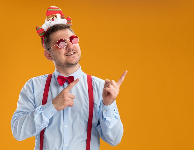 Gelukkig jonge man met bretels vlinderdas in rand met santa en rode bril wijzend met wijsvingers naar de zijkant staande over oranje achtergrond