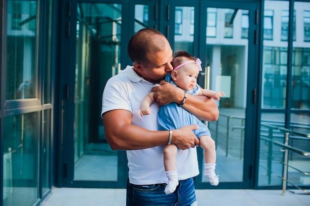 Gelukkig jonge man met een glimlachende 2-4 maanden oude baby tegen de achtergrond van de ingang van het huis. glazen gebouw