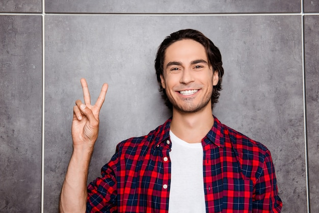 Gelukkig jonge man met een stralende glimlach met twee vingers
