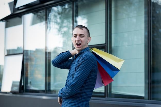 Gelukkig jonge man met kleurrijke boodschappentassen op straat. winkelcentrum
