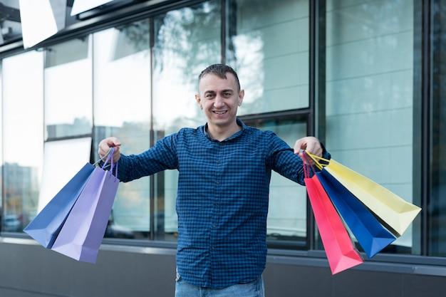 Gelukkig jonge man met kleurrijke boodschappentassen op straat