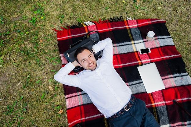 Gelukkig jonge man met laptop ontspannen op het gras, uitzicht vanaf de top