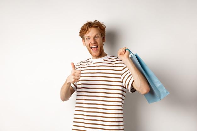 Gelukkig jonge man met rood haar, winkelen in winkels, duimen opdagen en papieren zak over schouder houden, winkel aanbevelen, witte achtergrond