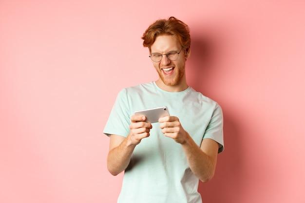 Gelukkig jonge man met rood rommelig kapsel, bril, videogame spelen op smartphone en plezier, mobiel scherm kijken, staande over roze achtergrond.