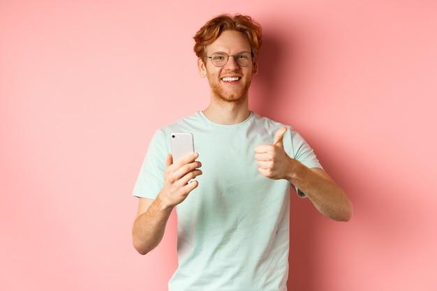 Gelukkig jonge man met rood slordig haar, duimen opdagen tijdens het gebruik van de mobiele telefoon, glimlachend en prijzende applicatie, staande op roze achtergrond.