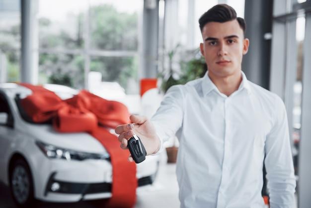 Gelukkig jonge man met sleutels in zijn handen, gelukkig een auto kopen.