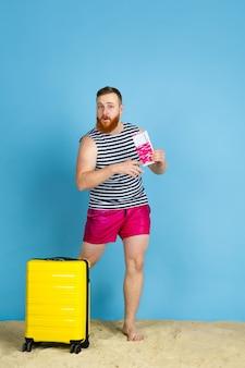 Gelukkig jonge man met tas voorbereid op reizen op blauwe ruimte