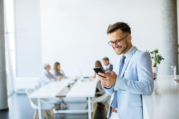 Gelukkig jonge man met zijn mobiele telefoon op kantoor en glimlachen terwijl zijn collega's op de achtergrond werken