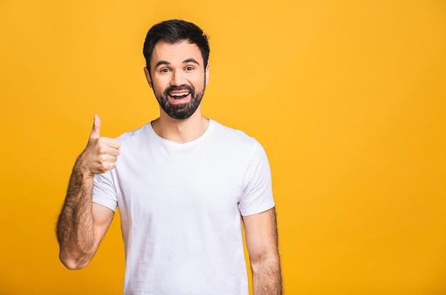 Gelukkig jonge man. portret van knappe jonge man glimlachend terwijl staande geïsoleerd op gele achtergrond. duimen omhoog.