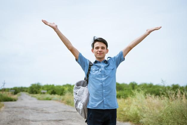 Gelukkig jonge man poseren met opgeheven armen op de weg staan en kijken in de verte gelukkige man in een blauw shirt met een rugzak gratis student geniet van vakantie
