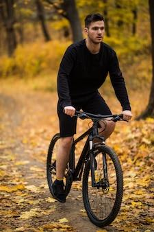 Gelukkig jonge man wielrenner rijdt in het zonnige bos op een mountainbike. avonturen reis.