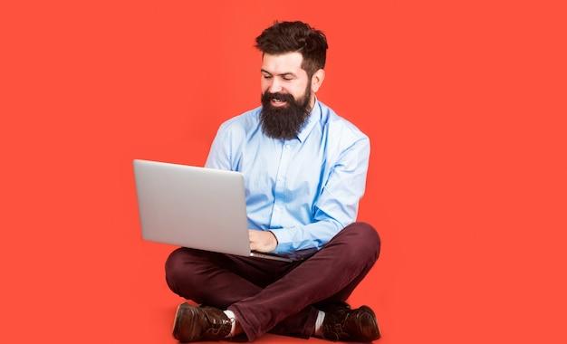 Gelukkig jonge man zittend op de vloer met laptopcomputer op rode achtergrond.