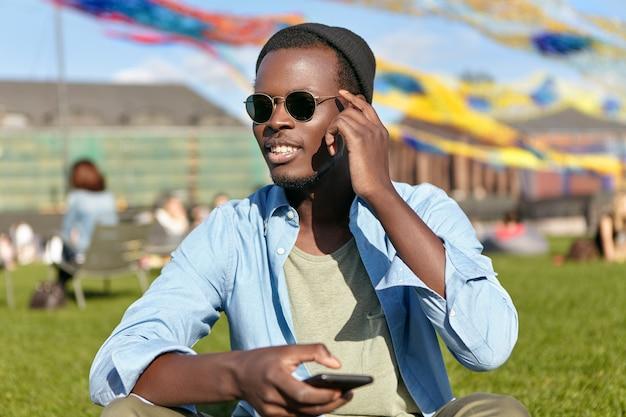 Gelukkig jonge man zittend op het gras met zijn telefoon