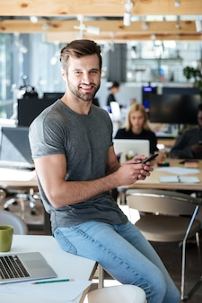 Gelukkig jonge man zittend op tafel in kantoor chatten