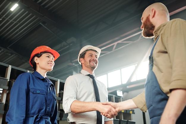 Gelukkig jonge meester groet zijn nieuwe ondergeschikte door handdruk in werkplaats met vrouwelijke ingenieur in de buurt