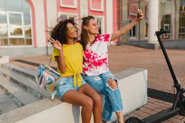 Gelukkig jonge meisjes vrienden glimlachend zittend in straat nemen selfie foto op mobiele telefoon, vrouwen samen plezier