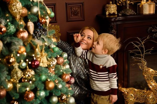 Gelukkig jonge moeder en haar zoon thuis met een kerstboom.