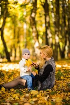 Gelukkig jonge moeder en haar zoontje tijd doorbrengen in de herfst park.