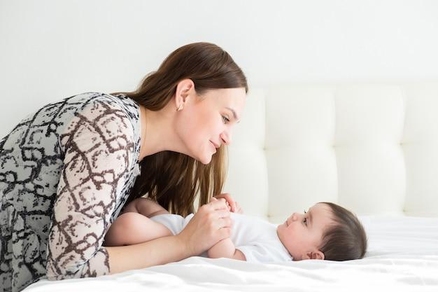 Gelukkig jonge moeder hand in hand haar dochtertje in bed. hou van levensstijl moederdag concept.