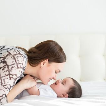 Gelukkig jonge moeder hand in hand haar dochtertje in bed.