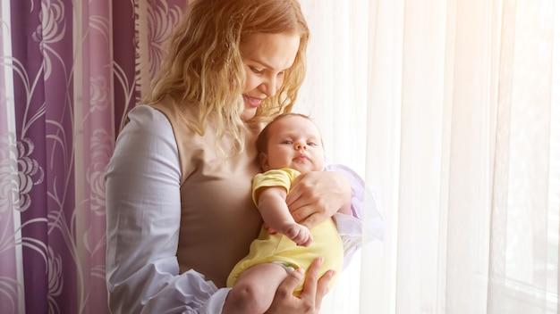 Gelukkig jonge moeder houdt babymeisje in armen zoenen bij raam