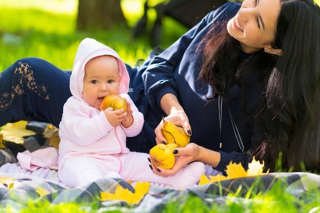 Gelukkig jonge moeder lachen om haar babymeisje als ze zit op een tapijt op het gras in een herfst park met een rijpe gouden appel