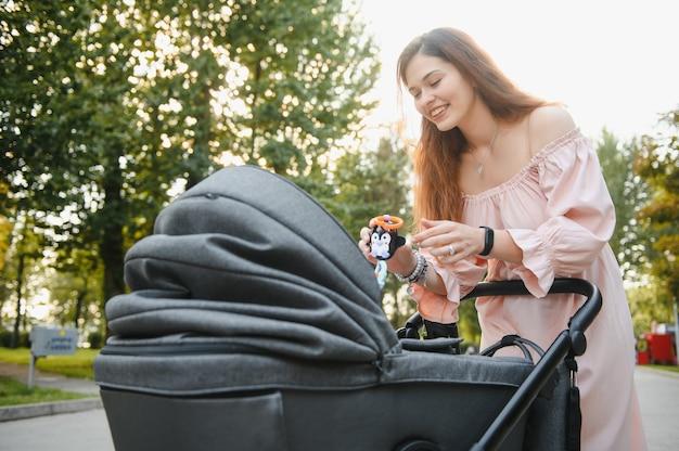 Gelukkig jonge moeder met baby in buggy wandelen in herfst park