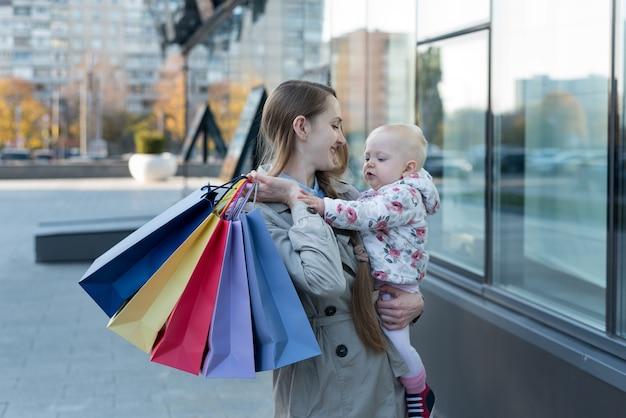 Gelukkig jonge moeder met dochtertje op de armen en boodschappentassen in de hand. shop dag.