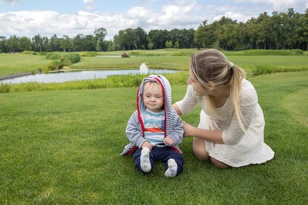 Gelukkig jonge moeder met haar 9 maanden oude babyjongen ontspannen op het gras in het park