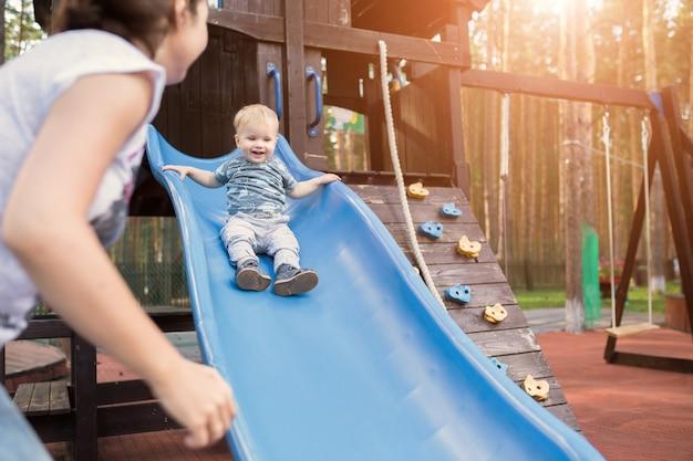 Gelukkig jonge moeder met haar babyjongen spelen in kleurrijke speeltuin voor kinderen. moeder met peuter die plezier heeft in het zomerpark. baby spelen in kinderglijbaan