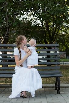 Gelukkig jonge moeder met mooie babymeisje op bankje. verticaal frame