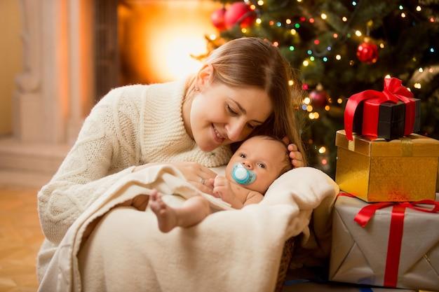 Gelukkig jonge moeder poseren met pasgeboren zoon onder kerstboom