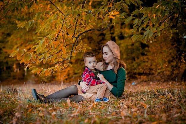 Gelukkig jonge moeder spelen en plezier maken met haar zoontje op zonnige warme herfstdag