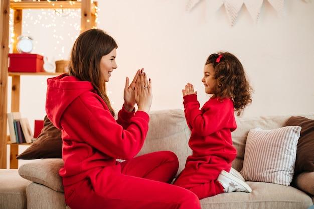 Gelukkig jonge moeder spelen met dochter op de bank. binnen schot van charmante moeder en preteen kind in rode kleding.
