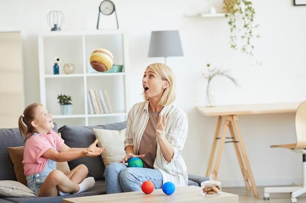 Gelukkig jonge moeder spelen met haar dochter met het syndroom van down op de bank in de woonkamer