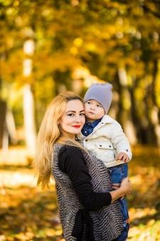 Gelukkig jonge moeder spelen met haar zoontje littlte op zonnige warme herfst- of zomerdag. prachtig zonsonderganglicht in de appeltuin of in het park. gelukkig gezin concept