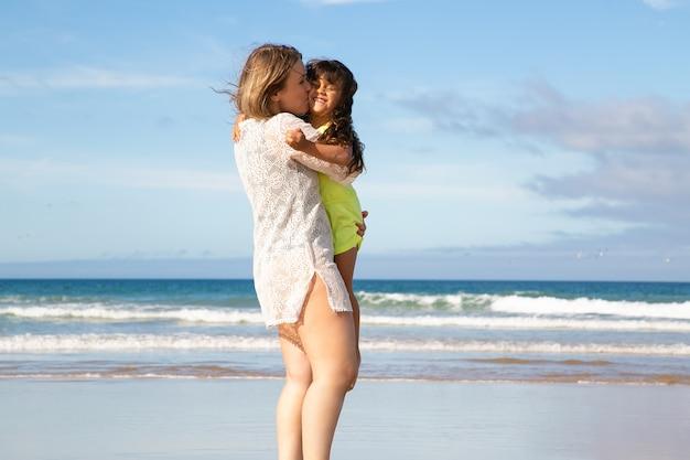 Gelukkig jonge moeder vrije tijd doorbrengen met dochtertje op strand op zee, kind in armen houden en kussen meisje