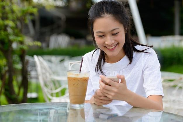 Gelukkig jonge mooie aziatische vrouw met behulp van telefoon in de coffeeshop buitenshuis