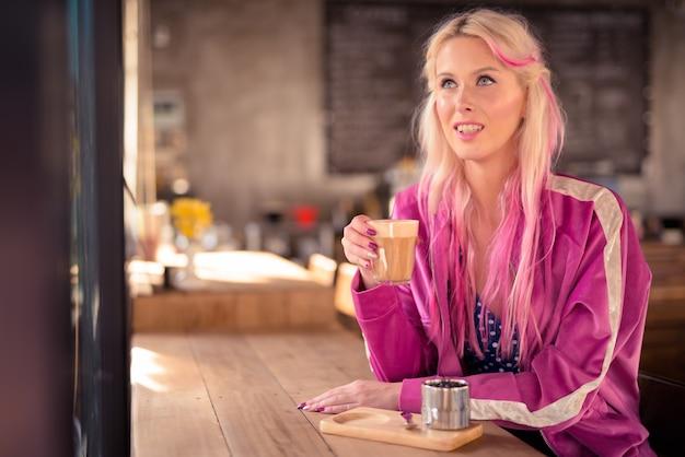 Gelukkig jonge mooie blonde vrouw denken en ontspannen in de koffieshop